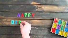 De luchtvideo van de tijdtijdspanne van de hand die van een kind een gelukkig verjaardagsbericht in gekleurde blokletters op hout stock videobeelden