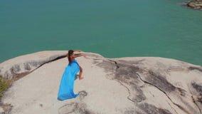 De luchtvrouw van de hommelmening in blauwe kleding die op van de klippen stammenfusie overzees als achtergrond, bungalow dansen stock video