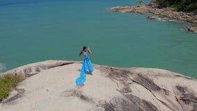 De luchtvrouw van de hommelmening in blauwe kleding die op van de klippen stammenfusie overzees als achtergrond, bungalow dansen stock videobeelden