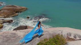 De luchtvrouw van de hommelmening in blauwe kleding die op van de klippen stammenfusie overzees als achtergrond, bungalow dansen stock footage