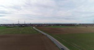 De luchtweg van de de Hommelinhoud van de Vogelmening met Licht Verkeer op Buitenstad en Akkerland stock videobeelden