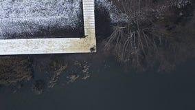 De luchtzitting van de meningsvisser op rivierpijler met hengel wachtende beet stock videobeelden