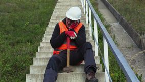 De luie arbeider met hamer ontspant op concrete treden stock videobeelden