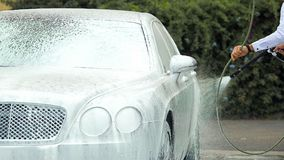 De luxeauto van de bedrijfsbestuurderswas met zeepsop alvorens werkgever op het werk te nemen stock afbeeldingen