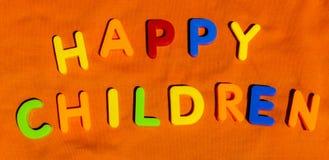 De lyckliga barnen för ord som är skriftliga vid leksakbokstäver Arkivbild