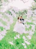 De lyckliga nygifta personerna är kyssande bak de pappers- svanarna i den gröna skogen royaltyfri bild