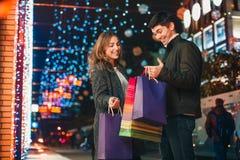 De lyckliga paren med shoppingpåsar som tycker om natt på stadsbakgrund Royaltyfri Foto