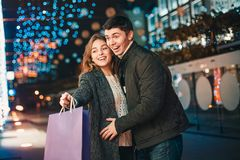 De lyckliga paren med shoppingpåsar som tycker om natt på stadsbakgrund Royaltyfri Bild