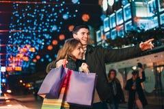 De lyckliga paren med shoppingpåsar som tycker om natt på stadsbakgrund Royaltyfria Bilder