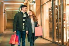 De lyckliga paren med shoppingpåsar som tycker om natt på stadsbakgrund Arkivfoton