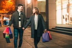 De lyckliga paren med shoppingpåsar som tycker om natt på stadsbakgrund Royaltyfri Fotografi
