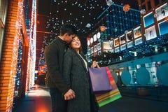 De lyckliga paren med shoppingpåsar som tycker om natt på stadsbakgrund Fotografering för Bildbyråer