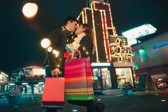 De lyckliga paren med shoppingpåsar som tycker om natt på stadsbakgrund Arkivfoto