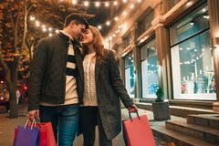 De lyckliga paren med shoppingpåsar som tycker om natt på stadsbakgrund Arkivbilder