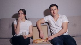 De lyckliga paren som äter en pizza och att hålla ögonen på en film på soffan lager videofilmer