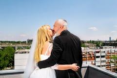 De lyckliga stiliga bröllopparen är stående och kyssa på taket Arkivfoto