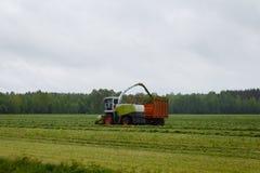 De maaimachine verzamelt droog gras royalty-vrije stock fotografie