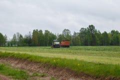 De maaimachine verzamelt droog gras aan de vrachtwagen in een gebiedshoogtepunt van groen gras stock afbeeldingen