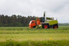 De maaimachine verzamelt droog gras aan de vrachtwagen op een gebied stock afbeeldingen