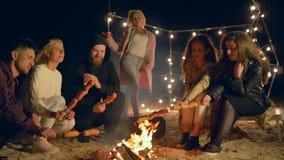 De maaltijd op Brand, jongeren roostert worsten bij kampvuur terwijl het ontspannen in openlucht bij nacht stock video