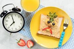 De maaltijd van het jonge geitjesontbijt, pindakaastoost met grappig gezicht royalty-vrije stock afbeelding