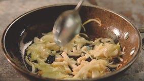 De de maaltijdchef-kok van de voedselkok voegt de gesneden pan van pijlinktvisuien toe stock footage