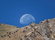 De maan die achter de berg plaatsen kijkt verbazend Royalty-vrije Stock Afbeeldingen