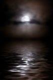 De maan in wolken boven een nightly meer, is een maanweg Stock Afbeeldingen