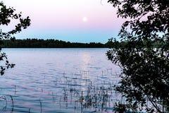 De maan wordt weerspiegeld in de oppervlakte van het meer Mooi nachtlandschap, achtergrond stock afbeelding