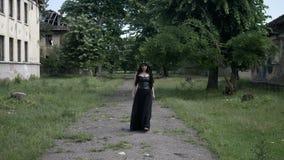 De macabere vrouw met gotische zwarte kleren en kroon van klimop verlaat het lopen onder geruïneerde gebouwen met kwaad uitdrukki stock footage