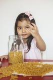 De macaroni van meisjesspelen Stock Fotografie