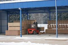 De machine heft timmerhout op een houten fabriek op stock afbeelding