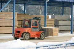 De machine heft timmerhout op een houten fabriek op royalty-vrije stock afbeelding