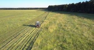De machine met roterende snijders maait gras op grond onder hemel stock videobeelden
