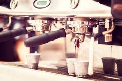 De machine van de koffie de koffiemachine verse koffie voorbereiden en in twee koppen bij restaurant gieten, de bar of de bar die Stock Foto