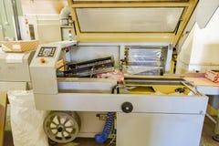 De machine van de voedselverpakking Verpakkingskoekjes in kartondozen en deklaag door film bij banketbakkerijproductielijn stock foto