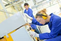 De machine van de vrouwenvestiging in fabriek stock afbeelding
