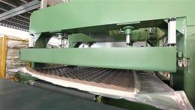 De machine voor vacuümverpakking van matrassen, vacuümverpakking van een matras, matras productie, installatie voor stock footage