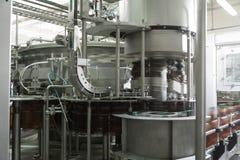 De machine vult plastic flessen bier op de bierfabriek Stock Foto