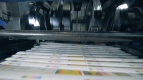 De machines die van het drukbureau krant op geautomatiseerde lijn bewegen stock videobeelden