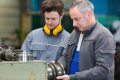 De Machines van ingenieursand apprentice using in Fabriek stock afbeeldingen