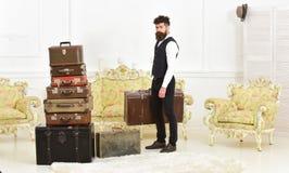 De macho elegant op strikt gezicht draagt uitstekende koffer Bagage en verhuizingsconcept Mens, butler met baard en stock foto's
