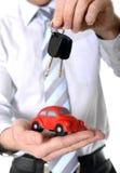 De macro rode stuk speelgoed auto met autosleutels bemant binnen hand Royalty-vrije Stock Foto's