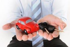 De macro rode stuk speelgoed auto met autosleutels bemant binnen hand Royalty-vrije Stock Afbeelding