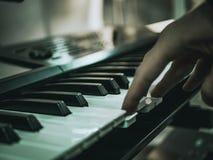 De macro schoot hand het spelen op de sleutels van de synthesizerpiano stock afbeeldingen