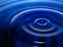De macrofotografie van een donkerblauwe waterdaling/een inkt laat vallen plons en rimpelingen, nat, conceptueel voor milieu, beho Stock Fotografie