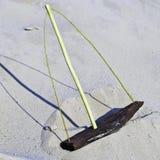 De madeira brinquedo-envie com um mastro em ondas arenosas. Imagem de Stock