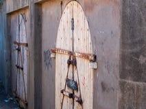 De madeira, os grafittis cobriram a porta fechado em um corredor traseiro fotografia de stock