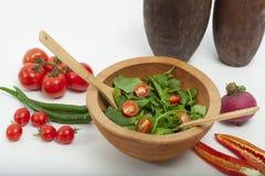 De madera en el piso, de madera en ensalada verde, tomate y pimienta Imagen de archivo libre de regalías