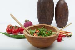 De madera en el piso, de madera en ensalada verde, tomate y pimienta Fotos de archivo
